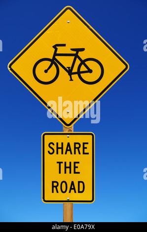 Partager la route avec les vélos panneau routier isolé avec fond de ciel bleu Banque D'Images