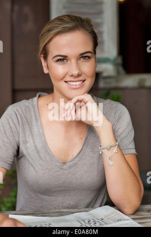Portrait of young woman sitting in cafe avec du papier journal Banque D'Images