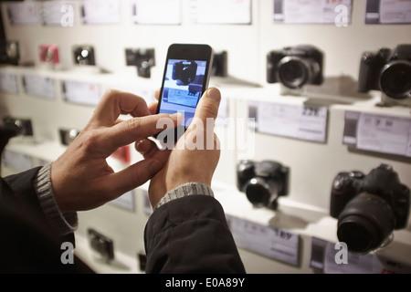 Mid adult man dans l'appareil photo à l'aide d'affichage boutique smartphone Blackberry Banque D'Images