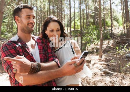 Jeune couple en forêt, homme pointant Banque D'Images
