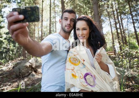 Jeune couple taking self portrait photograph in forest Banque D'Images