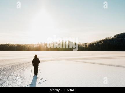 Homme mûr la marche nordique dans la neige champ couvert Banque D'Images