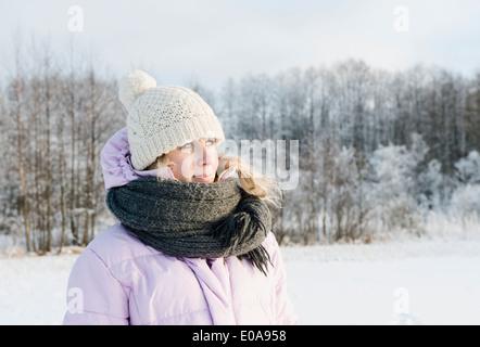 Mid adult woman wearing vêtements d'hiver dans le champ couvert de neige Banque D'Images