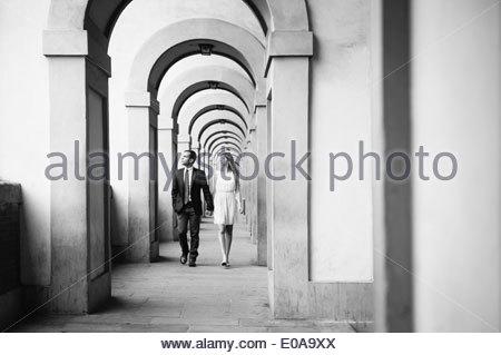 Couple marche main dans la main par arches dans Florence, Toscane, Italie Banque D'Images