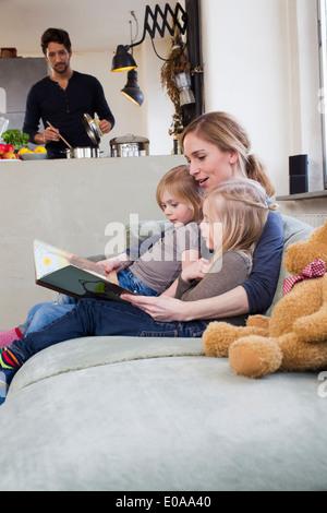 La mère et les deux filles lecture storybook Banque D'Images