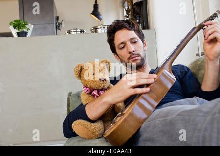 Mid adult man reclining on sofa à jouer de la guitare Banque D'Images