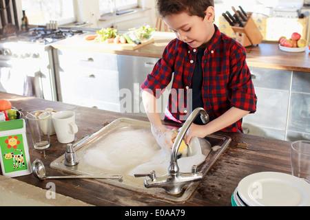 Jeune garçon dans la cuisine vaisselle Banque D'Images