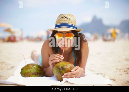 Portrait of young woman drinking from coconut, Ipanema beach, Rio de Janeiro, Brésil Banque D'Images