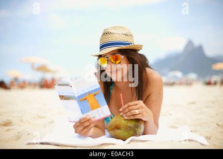 Young woman reading guide touristique, la plage d'Ipanema, Rio de Janeiro, Brésil Banque D'Images