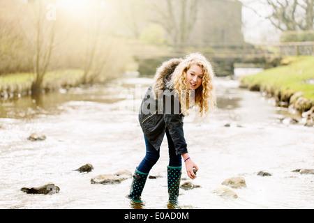Teenage girl picking des pierres dans la rivière rural Banque D'Images