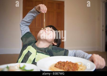 Garçon jouant avec des spaghetti Banque D'Images