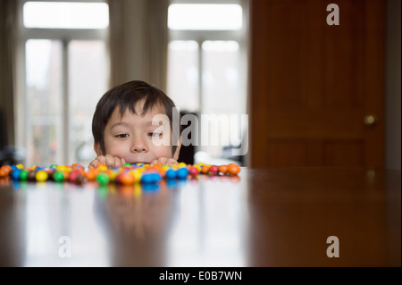 Boy peering over table à candy Banque D'Images