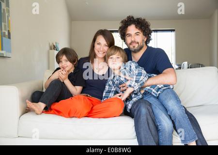 Portrait de famille avec deux garçons sur le canapé Banque D'Images