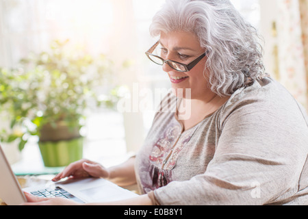 Young woman at home using laptop Banque D'Images