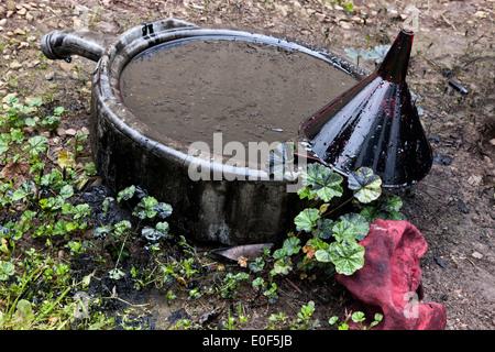 Bac de vidange d'huile contenant de l'huile moteur sale pollution des sols et de la flore. Banque D'Images