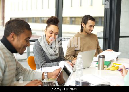 Young african american woman using laptop avec ses camarades de l'étude autour. Table de la bibliothèque de l'université Banque D'Images