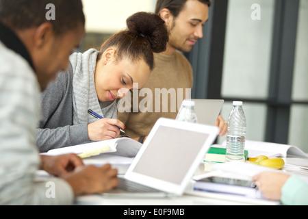 Young african american woman taking notes à partir de livres pour son étude. Les élèves assis à table avec des livres Banque D'Images