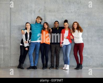 Groupe multiethnique de professionnels jeunes universitaires sur le campus. Mixed Race jeunes unis contre le mur.