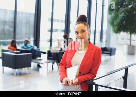 Certains jeunes afro american woman holding article par une rambarde regardant la caméra. Young businesswoman in Banque D'Images