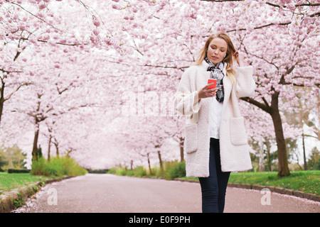 Jeune femme à l'écoute de la musique du parc printemps son téléphone mobile. Relaxed woman taking a walk at spring blossom garden. Banque D'Images