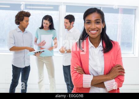 Businesswoman smiling to camera avec des collègues en arrière-plan Banque D'Images