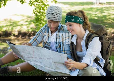 Couple actif assis sur une randonnée reading map Banque D'Images