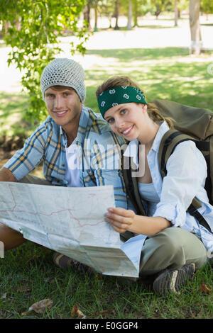Smiling couple actif assis sur une randonnée holding map Banque D'Images