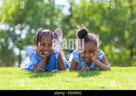 Outdoor portrait of a cute jeunes soeurs noir couché sur l'herbe et souriant - peuple africain Banque D'Images