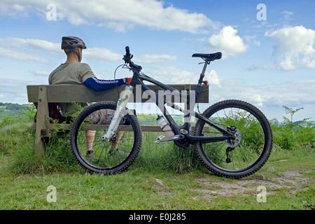 Vélo de montagne mâle posé sur un banc en bois. Banque D'Images