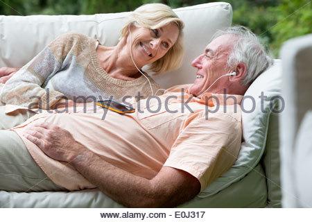 Senior couple listening to music on headphones on partagé piscine canapé Banque D'Images