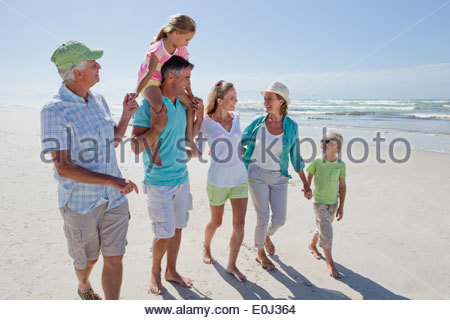Multi-generation family walking on sunny beach Banque D'Images
