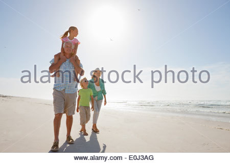 Les grands-parents et petits-enfants marchant sur sunny beach Banque D'Images