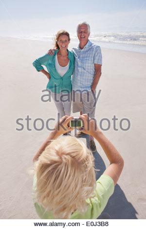Petit-fils avec appareil photo numérique en photographiant les grands-parents sur sunny beach Banque D'Images