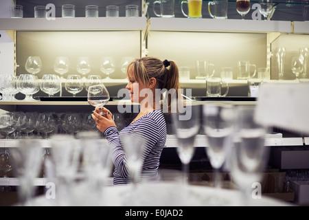 Young hispanic woman shopping pour les meubles, verres, vaisselle et décoration en magasin Banque D'Images