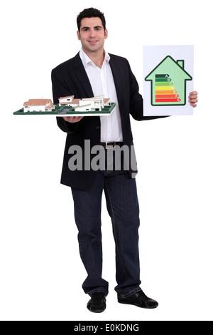 Homme tenant un modèle d'architecture et d'une étiquette de consommation d'énergie Banque D'Images