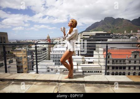 Belle jeune femme portant une chemise seulement avoir de tasse de café, profitant du soleil sur une chaude journée d'été.