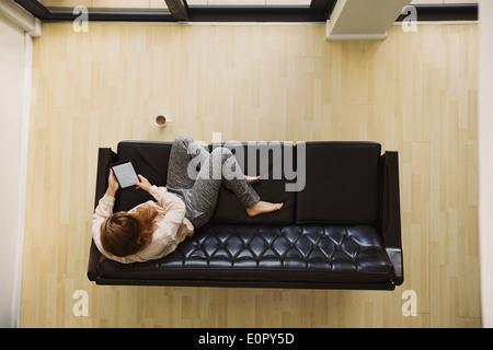Vue de dessus de jeune femme assise sur une table à l'aide de la tablette numérique. Female relaxing on sofa avec Banque D'Images