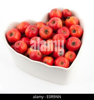 Pommettes dans un bol en forme de coeur Banque D'Images