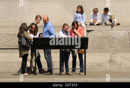 Londres, Angleterre, Royaume-Uni. Famille à la recherche d'information au conseil par la Colonne Nelson Banque D'Images