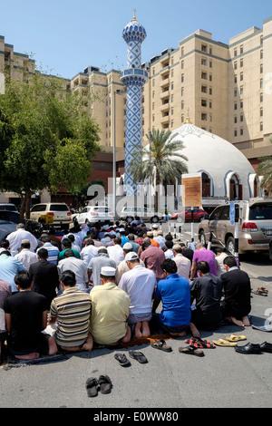 Beaucoup d'hommes prier le vendredi à la mosquée de l'extérieur du centre commercial Burjuman à Dubaï Émirats Arabes Banque D'Images