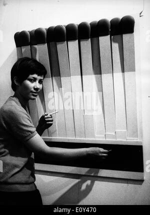 Jul 15, 1968; Munich, Allemagne; une femme fait semblant d'allumer une cigarette newx dans une grande boîte d'allumettes à une exposition d'art en Allemagne.