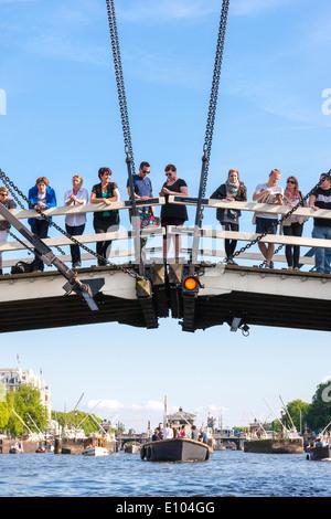 Amsterdam Magere Brug, Skinny Bridge, avec des gens touristes visiteurs observation des bateaux sur la rivière Amstel. Vu à partir de la croisière sur le canal.