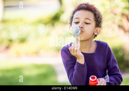 Mixed Race girl blowing bubbles outdoors Banque D'Images