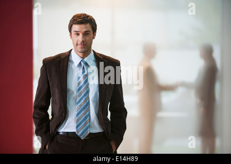 Businessman with hands in pockets in office Banque D'Images
