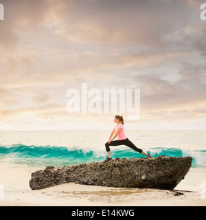 Caucasian runner stretching on beach Banque D'Images