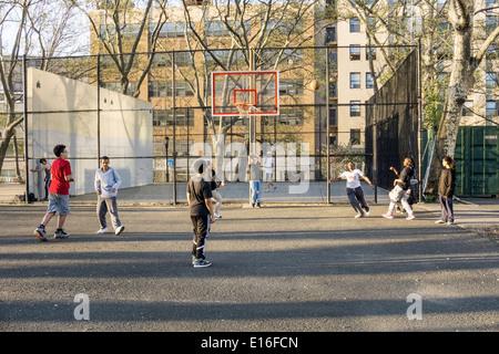 Teen black girl vise pour le panier dans un bon natured unisex street jeu de basket-ball dans DeWitt Clinton park Hells Kitchen
