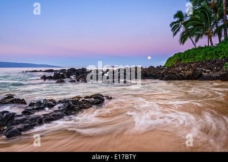 Lever du soleil avec la Lune plus belle et isolée Plage secrète à Maui, Hawaii. Banque D'Images