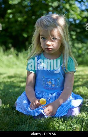 Petit enfant blond girl licking lollipop en extérieur dans jardin, portrait Banque D'Images