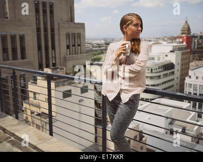 Belle Jeune femme debout près d'une balustrade sur terrasse tenant une tasse de café à la route. Les femmes de race blanche de boire du café.