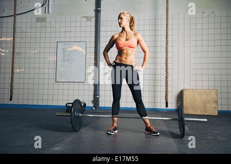 Full Length portrait of muscular young woman at gym à la voiture avec des barres au sol. Crossfit Forte femme au Banque D'Images